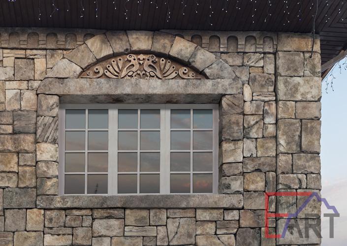 Барельеф на фасаде дома над окном в городе Видное