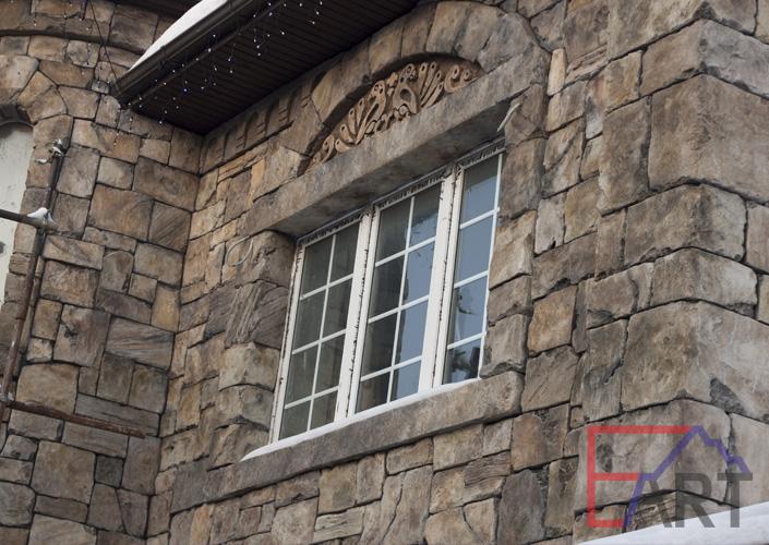 Барельеф на фасаде дома над окном