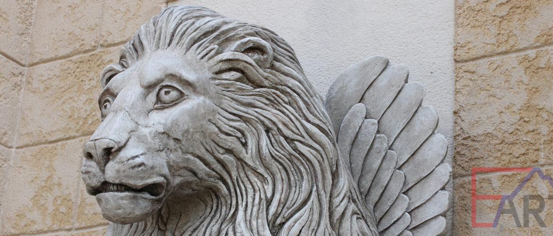 """Фрагмент скульптуры """"Лев"""" из архитектурного бетона на стене."""